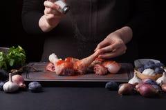 Żeński szef kuchni kropi świeżych surowych kurczaków drumsticks na ciemnym tle z morze solą Niedaleki kłamstwo składniki dla zdjęcia royalty free