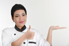 Żeński szef kuchni przedstawia menu Śliczny dziewczyna szef kuchni w kapiszonie pokazuje a Obraz Stock