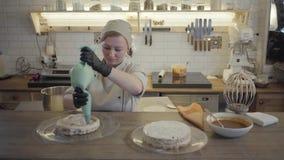Żeński szef kuchni przygotowywa tort w restauracyjnej kuchni w górę Kucharz dekoruje odgórną tortową warstwę od powiewnego zdjęcie wideo