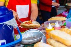 Żeński szef kuchni robi Laos stylowego baguette lub Francuskiego chleba sanwich, wysoce popularny śniadaniowy uliczny jedzenie w  zdjęcie stock