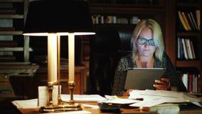 Żeński szef pracuje z pastylką w luksusowym biurze W tle jest półka z książkami, piękna stołowa lampa zdjęcie wideo