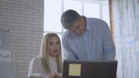 Żeński szef radzi męskiego kierownika pracownicy patrzeją w papiery i dyskutują projekt 4K zdjęcie wideo