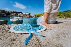 Żeński turystyczny obsiadanie na molu z blau słońca kapeluszem przy jej stroną w Assos wiosce przed szmaragd zatoką fotografia stock