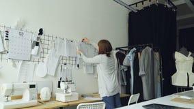 Żeński ubraniowy projektant bierze nakreślenia od studio stołu i stawia one na ścianie z innymi rysunkami kobiety ` s zbiory