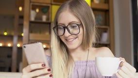 Żeński uczeń pije kawę w kawiarni z smartphone zdjęcie wideo