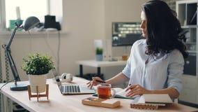 Żeński urzędnik używa laptop wtedy pisze informacji w notatniku zbiory wideo