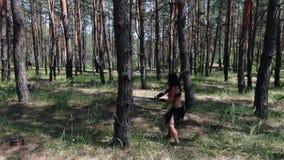 Żeński wojownik w czarnych skór ubraniach ćwiczy z kordzikiem na drzewie, 4k zbiory