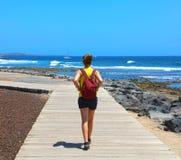 Żeński wycieczkowicza odprowadzenie na wybiegu z spektakularny krajobrazem Playa de Las Ameryki plaża, Tenerife, Hiszpania obraz stock