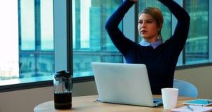 Żeński wykonawczy rozciąganie ona ręki podczas gdy pracujący w biurze zbiory wideo