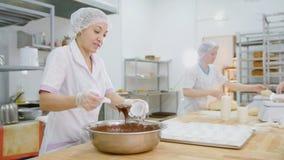 Żeńskich piekarnianych mieszanek czekoladowa śmietanka w metalu robić i pucharze zasycha zdjęcie royalty free