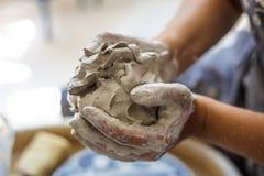 Żeńskie garncarek ręki ugniatają mokrą białą glinę Zdjęcia Royalty Free