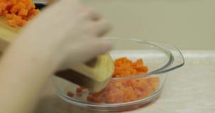 Żeńskie gospodyń domowych ręki stawiają kawałki pokrojona marchewka w sałatkowego talerz zdjęcie wideo