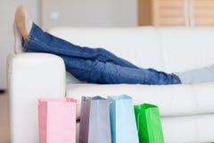 Żeńskie nogi odpoczywa na kanapie po robić zakupy wycieczkę turysyczną Zdjęcie Stock