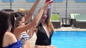 Żeńskie nogi w basenie robią pluśnięciom i cieszyć się koktajlowi na gorącym słonecznym dniu zdjęcie wideo
