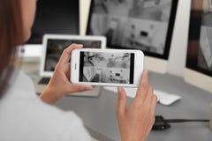 Żeńskie pracownika ochronego monitorowanie domu kamery używać smartphone indoors obrazy stock