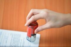 Żeńskie ręka chwyta pieczątki nad dokumentami i papierami przy biuro stołem, zbliżenie szczegółu krótkopęd Zdjęcie Royalty Free