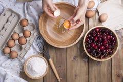 Żeńskie ręki łamają jajko w drewnianego puchar Przygotowanie ciasto dla kulebiaka z wiśnią Lat domowej roboty ciasta Odgórny wido obrazy royalty free