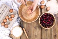 Żeńskie ręki łamają jajko w drewnianego puchar Przygotowanie ciasto dla kulebiaka z wiśnią Lat domowej roboty ciasta Odgórny wido obraz royalty free