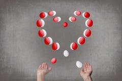Żeńskie ręki żonglują jajka w postaci walentynki ` s serca szef kuchni pojęcia karmowa świeża kuchni oleju oliwka nad dolewania r fotografia stock