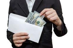 Żeńskie ręki biorą za dolarach od białej koperty Bia?y t?o zdjęcie stock