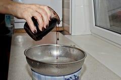 Żeńskie ręki nalewać przyskrzyniają od słoju w puchar przez arfy przeciw tłu kuchenny wnętrze Piec, gotuj?cy obraz royalty free