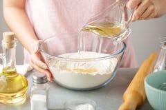 Żeńskie ręki nalewają olej w puchar z mąką, wypiekowym proszkiem i solą, zdjęcie stock