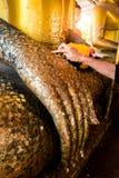 Żeńskie ręki są ozłacającym Buddha statuą Obrazy Stock