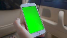 Żeńskie ręki scrolling na smartphone z zieleń ekranem, chroma kluczowy alfa kanał zbiory