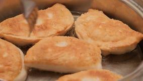 Żeńskie ręki smażą pasties z serem, mięso, cebule w wielkiego kucharstwo garnka kocioł w oleju Gospodyni domowa piec chebureks w  zbiory