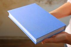 Żeńskie ręki trzyma książkowymi w błękit pokrywie Obrazy Stock