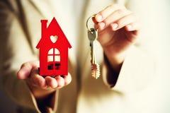 Żeńskie ręki trzyma małą czerwień mieścą i klucze Agent nieruchomości oferta ty mieścisz lub mieszkanie Majątkowy ubezpieczenie i Obraz Royalty Free