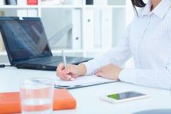 Żeńskie ręki trzyma srebnego pióra closeupand writing biznesowa kobieta robi notatkom przy biurowym miejscem pracy Biznesowa prac Fotografia Royalty Free