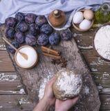 Żeńskie ręki trzymają świeżo przygotowanego ciasto dla domowej roboty ciastka z śliwkami nad stołami z składnikami dla kulebiaka zdjęcie royalty free