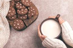 Żeńskie ręki trzymają filiżankę ciepły mleko, czekoladowi ciastka dalej obraz stock