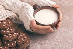 Żeńskie ręki trzymają filiżankę ciepły mleko, czekoladowi ciastka dalej fotografia royalty free