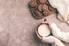 Żeńskie ręki trzymają filiżankę ciepły mleko, czekoladowi ciastka dalej zdjęcie royalty free