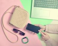 Żeńskie ręki używają smartphone na tle torba, laptop Obrazy Stock