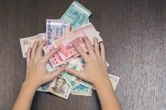 Żeńskie ręki utrzymują plika naciskają drewniany stół Azja Południowo-Wschodnia pieniądze banknotów pojęcia korupci dolarowej kop Zdjęcia Stock