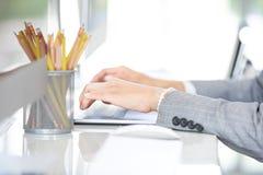 Żeńskie ręki w kostiumu działaniu używają komputer na białym stole wewnątrz obraz stock