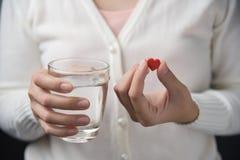 Żeńskie ręki z białą koszula trzymają czerwoną pigułkę w kierowym kształcie zdjęcia royalty free