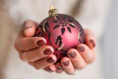 Żeńskie ręki z brązu gwoździa połyskiem robią manikiur mienie czerwoną Bożenarodzeniową piłkę obraz royalty free
