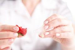 Żeńskiego chwyta otwarty kondom w rękach, antykoncepcyjny pojęcie Zdjęcie Royalty Free