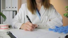 Żeńskiego dentysty mienia stomatology fachowy narzędzie i wskazywać przy zębami modelujemy stomatologiczny higieny i zdrowie poj? zdjęcie wideo