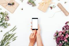 Żeńskiego mienia mądrze telefon w rękach wśród prezentów Fotografia Stock