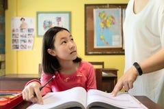Żeńskiego nauczyciela nauczania uczeń przy szkołą, nauczyciel małej dziewczynki pomaga studiowanie przy biurkami z ich pracą domo obrazy royalty free