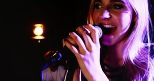 Żeńskiego piosenkarza śpiew w mikrofon 4k zbiory