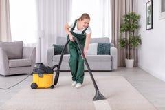 Żeńskiego pracownika cleaning dywan z próżnią obrazy royalty free