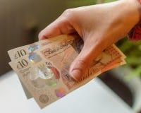 Żeńskiego ręka chwyta 10 funtów Nowa notatka A Zdjęcia Stock