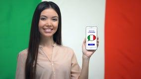 Żeńskiego ucznia mienia telefon z językowym nauki app, włoszczyzny flaga na tle zbiory wideo