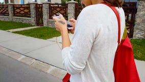 Żeńskiego ucznia słuchawki patrzeje w smartphone app, chodząca ulica, życia niebezpieczeństwo zdjęcie royalty free